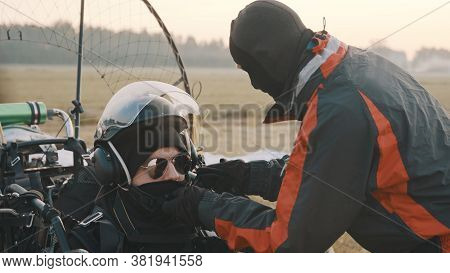 Paramotorgliding. Successfully Landed, Glider Helping Friend With Mask.