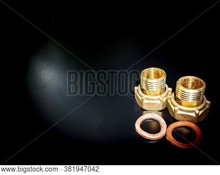 Nuts With Gaskets For Connecting Water Pipes. Black Background. Plumbing Equipment. Plumbing Repair.