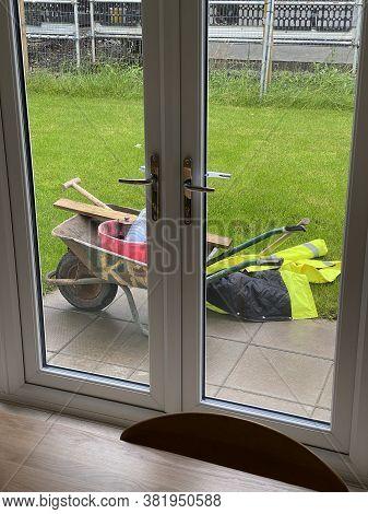 Gardening Equipment And Wheelbarrow In Yard Garden