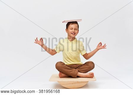 Small Boy Holds Book On His Head While Balancing On Special Simulator For Training Muscles. Child Is