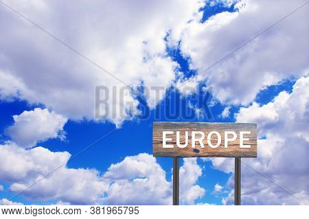 Europe Sign On Wooden Plate. Sign With Inscription Europe With View Of Sky. Road Sign On Wooden Tabl
