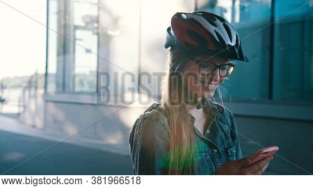 Happy Caucasian Woman With Helmet Rollerblading Through The City And Checking The App On The Smartph