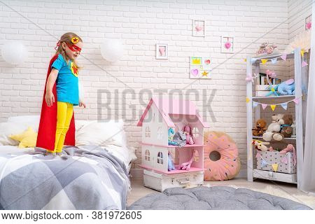 Brave Cute Little Girl Wants To Jump Out Bed, Imagining Flight. Child Plays Superhero With Cape And
