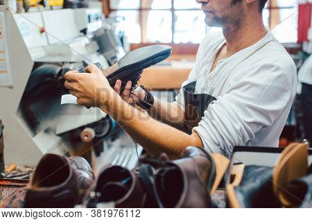 Shoemaker roughing the sole of a leather shoe at the machine