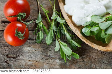 Fresh Purslane (portulaca Oleracea), Edible Weeds With Yoghurt And Cherry Tomatoes On Wooden Table.