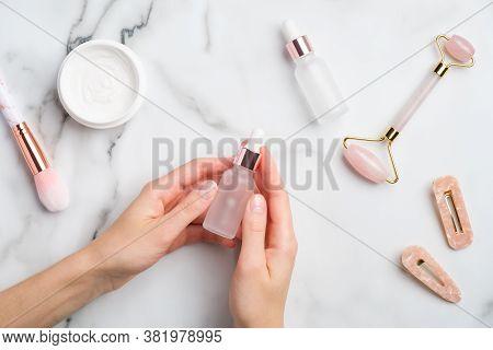 Female Hand Holding Serum Bottle Over Marble Table With Moisturizer Cream, Makeup Brush, Face Massag