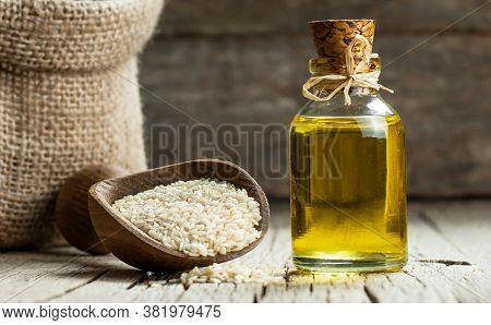 Glass Bottle Of Sesame Oil And Raw Sesame Seeds In Wooden Spoon Or Scoop On Rustic Table. Uncooked S