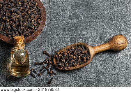 Close Up Glass Bottle Of Clove Oil And Cloves In Wooden Spoon On Wooden Table. Essential Oil Of Clov