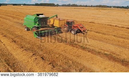 Warsaw Poland 10 August 2020 Harvesting Season. Combine Harvester And Tractor With The Trail Working