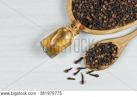 Close Up Glass Bottle Of Clove Oil And Cloves In Wooden Spoon On Rustic Table. Essential Oil Of Clov