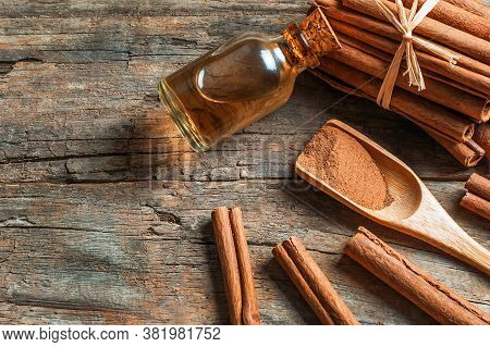 Close Up Bottle Of Cinnamon Oil With Cinnamon Sticks On Wooden Background, Healthy Spice Concept