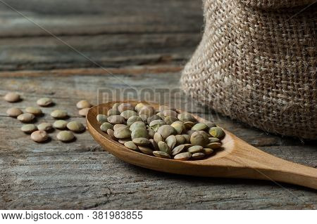 Green Lentils In Wooden Spoon Or Shovel On Wooden Background. Uncooked Green Lentil Legumes, Herbace