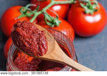 Tomato Paste In Wooden Spoon And Ripe Fresh Grape Tomatoes On Wooden Background. Cherry Tomatoes. To