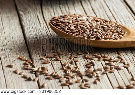 Heap Of Flax Seeds Or Linseeds In Spoon On Wooden Backdrop. Flaxseed Or Linseed Concept. Flax Seed D