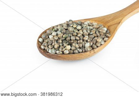 Heap Of Dried Organic Hemp Seeds Or Cannabis Plant Seeds In Wooden Spoon Isolated On White Backgroun