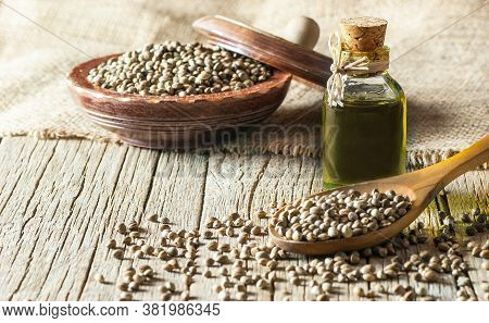 Heap Of Dried Organic Hemp Seeds Or Cannabis Plant Seeds In Spoon And Bowl With Glass Of Hemp Seed O