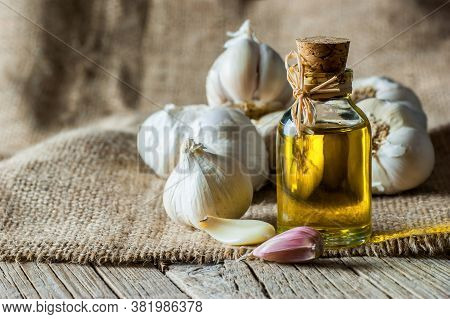 Ripe And Raw Garlic And Garlic Oil In Glass Of Bottle On Wooden Table With Burlap Sack, Alternative