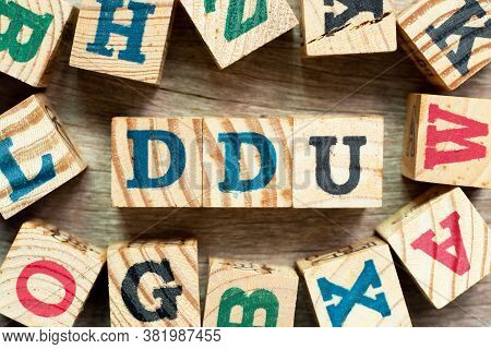 Alphabet Letter Block In Word Ddu (abbreviation Of Delivered Duty Unpaid) With Another On Wood Backg