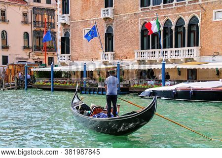 Gondolier Rowing Gondola With Tourists On Grand Canal In Venice, Italy. Venice Is Situated Across A
