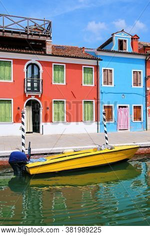 Boat Anchored In Canal In Burano, Venice, Italy. Burano Is An Island In The Venetian Lagoon And Is K