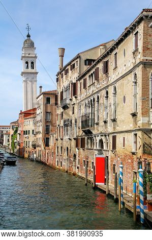 Narrow Canal Lined With Houses In Venice, Italy. Venice Is Situated Across A Group Of 117 Small Isla