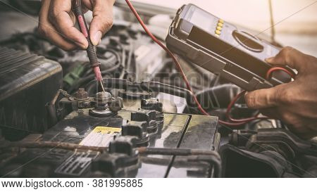 Auto Mechanic Using Measuring Equipment Tool For Fix Checking Car Battery. Concepts Of Old Car Repai