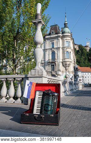 Ljubljana, Slovenia - August 13, 2020: Piano Accordion And Slovenian Flag On The Three Bridges In Lj
