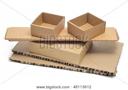 some brown cardboard boxes of different sizes and some pieces of corrugated cardboard on a white background