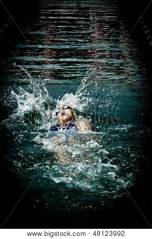Girl swimming backstroke outdoors in competition