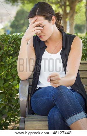 Upset Young Woman Sitting Alone on Bench Outside with Her Head in Her Hand and Clinched Fist.