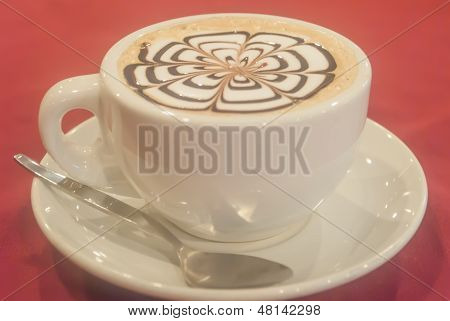 Cup Of Cappuccino Over Red Table