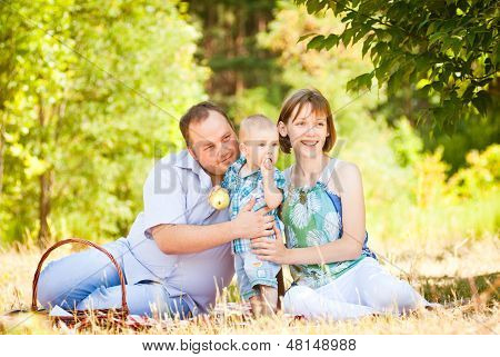 Mom, dad and son have a picnic