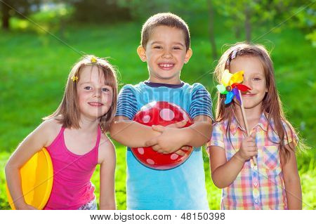 Three smiling kids in a summer park