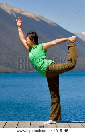 A Girl Yogaing By The Lake