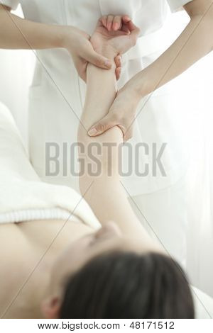 The esthetician who massages an arm