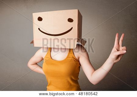 Young man standing and gesturing with a cardboard box on his head with smiley face poster