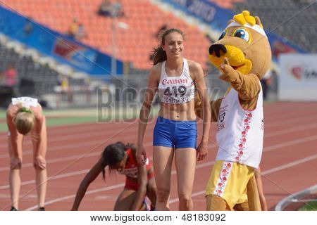 DONETSK, UKRAINE - JULY 14: World Youth Champion in 800 meters Hinriksdottir, Iceland accept congratulations from the mascot of 8th IAAF World Youth Championships in Donetsk, Ukraine on July 14, 2013