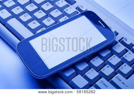 Smartphone On The Computer Keyboard