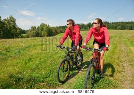 Sportive Couple Riding Mountain Bike In Meadow