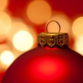Red Christmas bauble with blured lights in background very shallow DOF poster