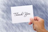 A hand holding a thank you card on a blue background thank you card poster