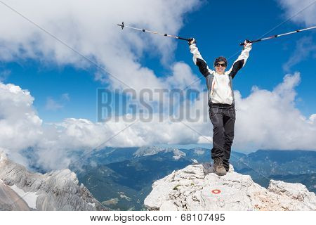 Female climber standing on top of a mountain and celebrating her successful ascend poster