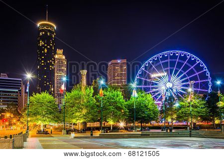 Ferris Wheel And Buildings Seen From Centennial Park At Night In Atlanta, Georgia.