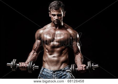 athletic young caucasian man in studio on black background with dumbellss poster