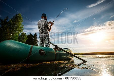 Mature man fishing from the boat at sunset