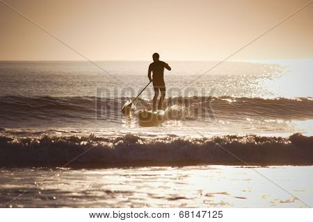 Silhouette of a man paddle boarding