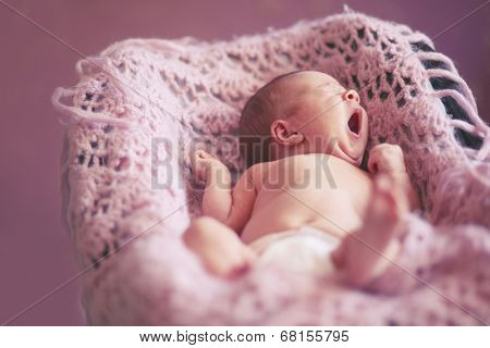 Portrait of a cute newborn baby girl lying down on a blanket