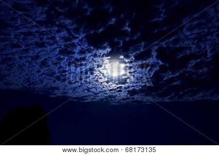 Full moon glowing in night sky illuminating cloud cover