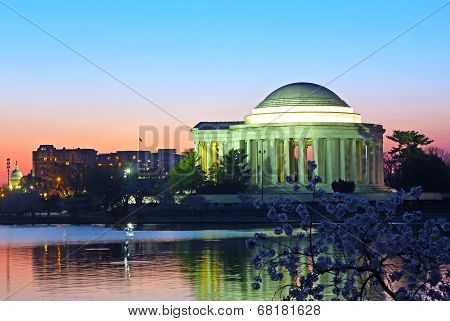 Thomas Jefferson Memorial and Capitol Building at predawn during cherry blossom festival.