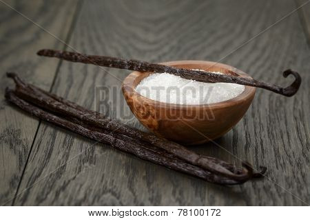 Bourbon Vanilla Pods With White Sugar On Wood Table